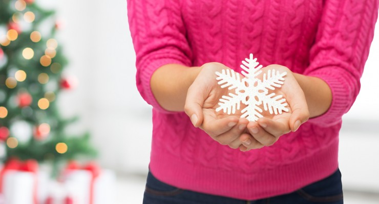 close up of woman holding snowflake decoration