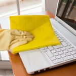 hand with yellow glove cleaning a laptop