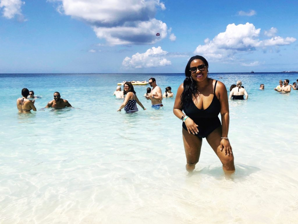 Black woman in bathing suit on beach in Grand Cayman