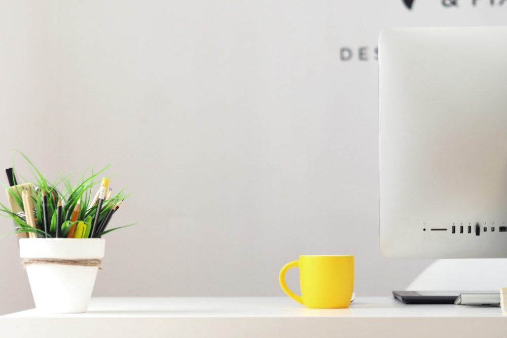 Workplace desktop with iMac, flowers, and a cup of coffee.